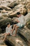 Отец и сын играют на утесах стоковые фото