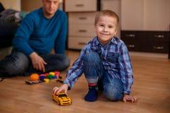 Отец и сын играют с уроками машин игрушек с ребенком стоковые изображения rf