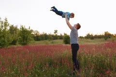 Отец и сын играя весной поле на времени захода солнца Люди имея потеху на поле Концепция дружелюбного Стоковое фото RF