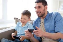 Отец и сын играя видеоигру дома Стоковые Изображения