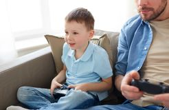 Отец и сын играя видеоигру дома Стоковые Фото