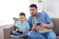 Отец и сын играя видеоигру дома Стоковые Изображения RF