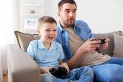 Отец и сын играя видеоигру дома Стоковая Фотография
