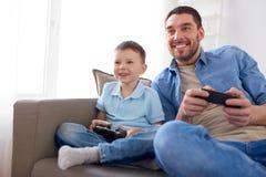 Отец и сын играя видеоигру дома Стоковое Фото