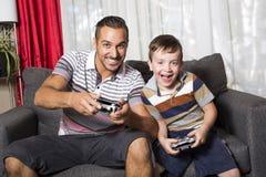 Отец и сын играя видеоигру Стоковые Фото