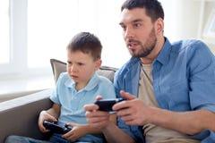 Отец и сын играя видеоигру дома Стоковые Фотографии RF