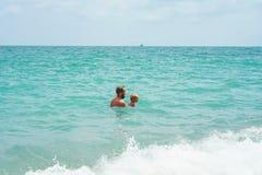 Отец и сын играя в море стоковая фотография