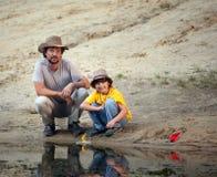 Отец и сын играя в шлюпках на речном береге, семья va Стоковые Изображения