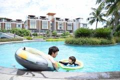 отец и сын играя на бассейне лета Стоковые Изображения