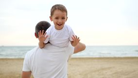 Отец и сын играя на песочном seashore Человек продолжает его плечо счастливый смеясь мальчик который развевает его руки видеоматериал