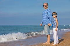 Отец и сын играя на пляже на времени дня Концепция  Стоковые Фотографии RF
