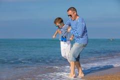 Отец и сын играя на пляже на времени дня Концепция  Стоковые Фото