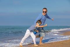 Отец и сын играя на пляже на времени дня Концепция  Стоковая Фотография