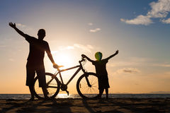 Отец и сын играя на пляже на времени захода солнца Стоковые Изображения
