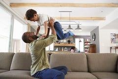 Отец и сын играя на софе в салоне совместно стоковое фото rf