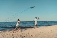 отец и сын играя со змеем на пляже стоковое изображение