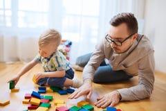 Отец и сын играя с блоками игрушки дома Стоковая Фотография