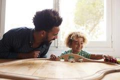 Отец и сын играя с комплектом поезда игрушки Стоковые Изображения