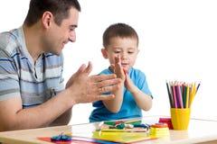 Отец и сын играя с пластилином стоковое изображение