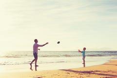Отец и сын играя футбол задвижки бросая Стоковые Изображения RF