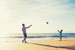 Отец и сын играя футбол задвижки бросая Стоковое Фото