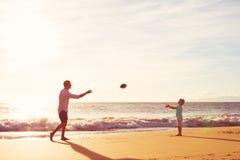 Отец и сын играя футбол задвижки бросая Стоковая Фотография RF