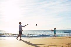 Отец и сын играя футбол задвижки бросая Стоковая Фотография