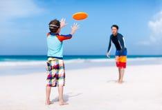 Отец и сын играя frisbee стоковые фотографии rf