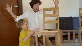 Отец и сын имеют промежуток времени потехи собрать деревянную мебель от небольших частей Мальчик помогает его отцу собрать a акции видеоматериалы