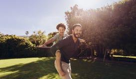 Отец и сын имея потеху играя в парке стоковое изображение rf