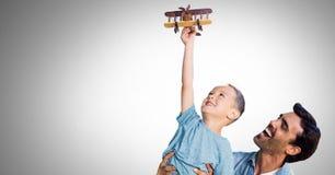 Отец и сын имея потеху играя с предпосылкой виньетки Стоковые Изображения
