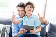 Отец и сын используя таблетку цифров стоковые изображения