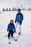 Отец и сын, катаясь на лыжах в зиме, мальчик уча кататься на лыжах, идущ Стоковое фото RF