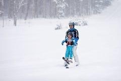 Отец и сын, катаясь на лыжах в зиме, мальчик уча кататься на лыжах Стоковая Фотография