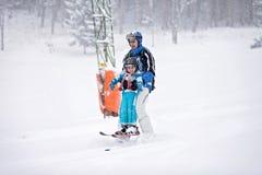Отец и сын, катаясь на лыжах в зиме, мальчик уча кататься на лыжах Стоковое Изображение
