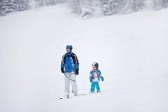 Отец и сын, катаясь на лыжах в зиме, мальчик уча кататься на лыжах Стоковые Изображения