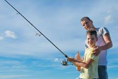 Отец и сын который держит рыболовную удочку для того чтобы уловить рыб и показывает его руку хорошо, против голубого неба стоковые фотографии rf