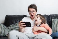 Отец и сын наблюдая страшное видео по телефону сидя на софе на белой предпосылке Они кричащий Мальчик и стоковое фото rf