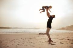 Отец и сын наслаждаясь праздниками на береге моря Стоковые Изображения RF