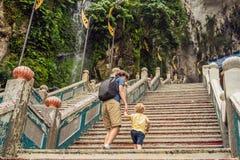 Отец и сын на заднем плане Batu выдалбливают, около Куалаа-Лумпур, Малайзию Путешествовать с концепцией детей стоковые изображения