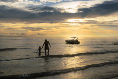 Отец и сын на заходе солнца на море Стоковые Фотографии RF