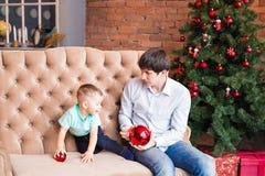 Отец и сын на предпосылке интерьера рождества Стоковая Фотография