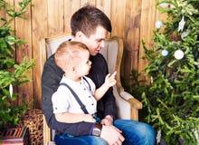 Отец и сын на предпосылке интерьера рождества Стоковые Фотографии RF