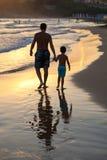 Отец и сын на пляже на заходе солнца стоковые фото