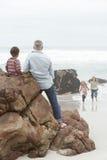 Отец и сын на утесе при девушки бежать в воде Стоковые Фото