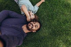 Отец и сын ослабляя в парке лежа на земле стоковое фото