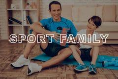 Отец и сын отдыхают на ковре спортзала стоковые фото
