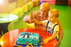 Отец и сын отрезали день рождения торта стоковая фотография rf