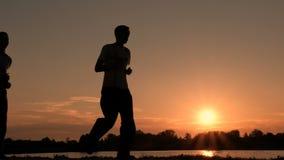 Отец и сын принимансяы за утро побежать на обваловке на восходе солнца Силуэт 2 людей бежать вдоль банка r сток-видео
