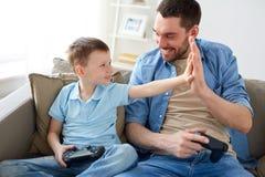 Отец и сын при gamepads делая максимум 5 Стоковое фото RF
